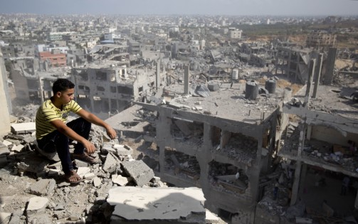 A Palestinian man looks out over destruction in part of Gaza City's al-Tufah neighbourhood as the fragile ceasefire in the Gaza Strip entered a second day on August 6, 2014 while Israeli and Palestinian delegations prepared for crunch talks in Cairo to try to extend the 72-hour truce. The ceasefire, which came into effect on August 5, has brought relief to both sides after one month of fighting killed 1,875 Palestinians and 67 people on the Israeli side. AFP PHOTO / MAHMUD HAMS